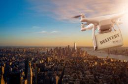 Multicopter,Drone,Flying,With,Package,Over,The,Cityscape,Of,Lower